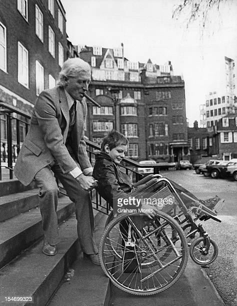 English dj and television presenter Jimmy Savile with a former patient at Stoke Mandeville Hospital 23rd January 1980 Savile has just launched a ten...