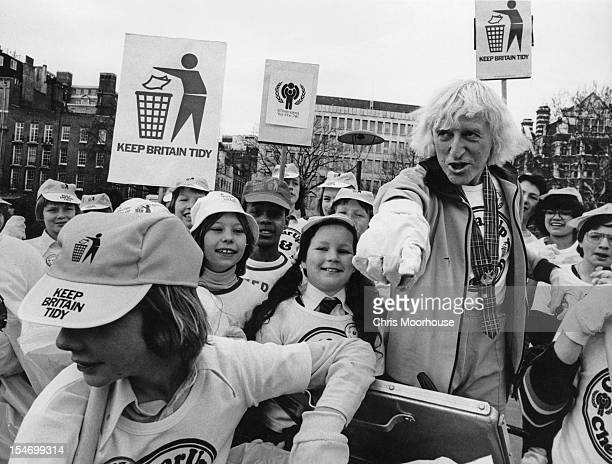 English dj and television presenter Jimmy Savile with a group of children during a 'Keep Britain Tidy' campaign event 6th March 1979