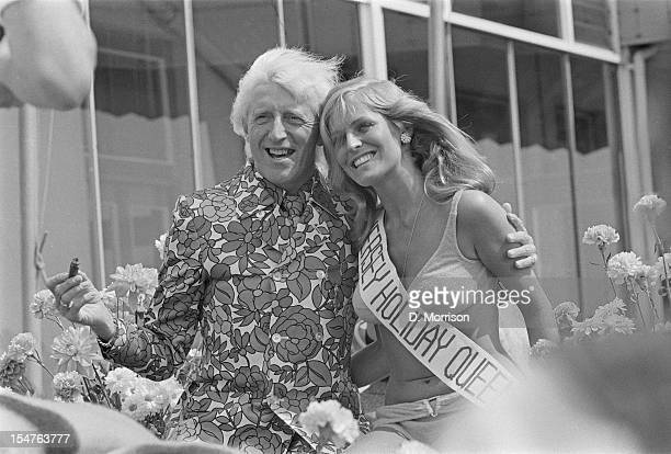 English dj and television presenter Jimmy Savile with 'Jersey Holiday Queen' Gaynor Lacey at the Jersey Battle of Flowers carnival Jersey 3rd August...