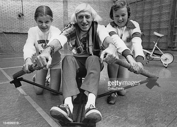 English dj and television presenter Jimmy Savile with pupils at the William Gladstone High School in Brent London 20th October 1977 Savile is at the...