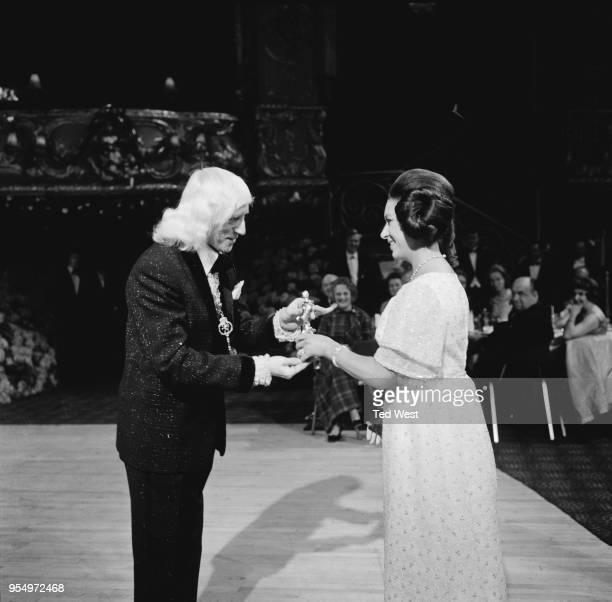 English DJ Jimmy Savile receives the Carl Alan award for top disc jockey of 1969 from Princess Margaret at the Lyceum Ballroom in London 18th March...