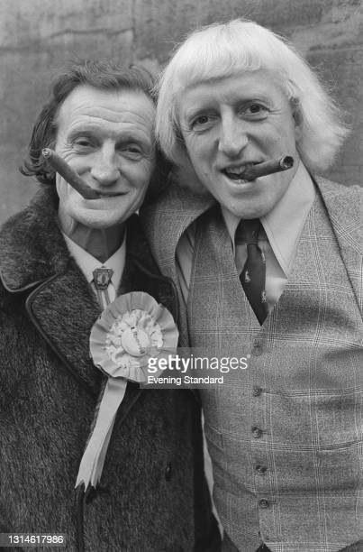 English DJ Jimmy Savile with his brother Johnnie Savile, a candidate for the Liberal Party in the Battersea North constituency, during the UK general...