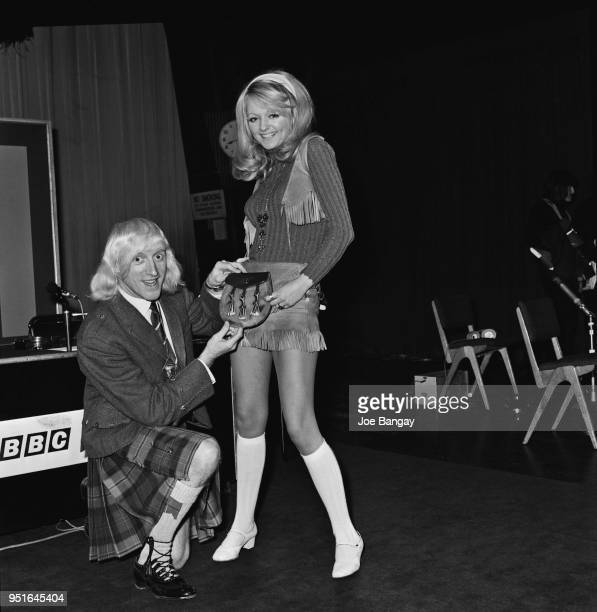 English DJ television and radio personality dance hall manager Jimmy Savile with Karen Kerr at BBC to broadcast radio programme 'Speakeasy' UK 14th...