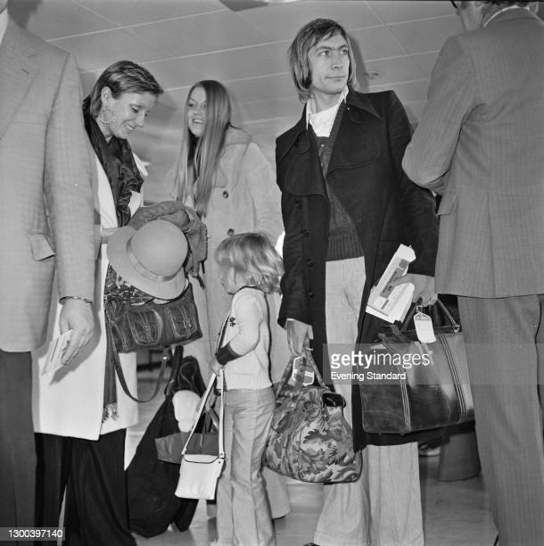 English drummer Charlie Watts of rock group the Rolling Stones at Heathrow Airport in London with his wife Shirley and their daughter Seraphina, UK,...