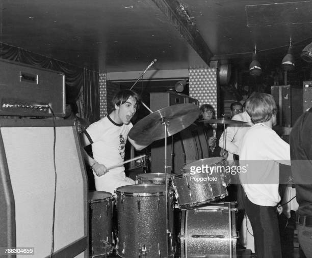 English drummer Keith Moon of mod rock group The Who performs live on stage playing his drum kit at a small club venue during a tour of the United...