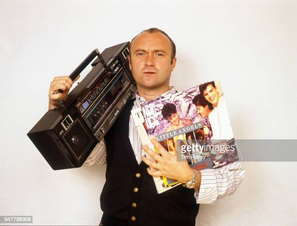 English drummer singersongwriter record producer and actor Phil Collins of rock band Genesis holding a portable radio and some records during a photo...