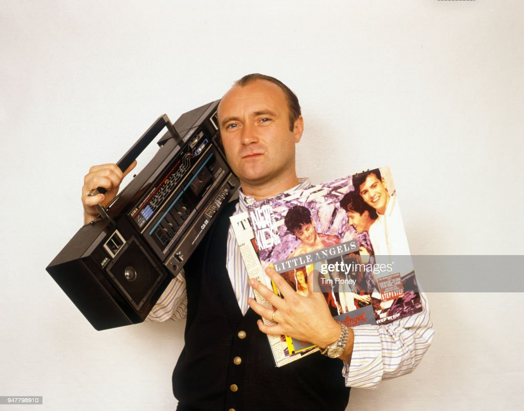 English drummer, singer-songwriter, record producer and actor Phil Collins of rock band Genesis, holding a portable radio and some records during a photo shoot, circa 1995.
