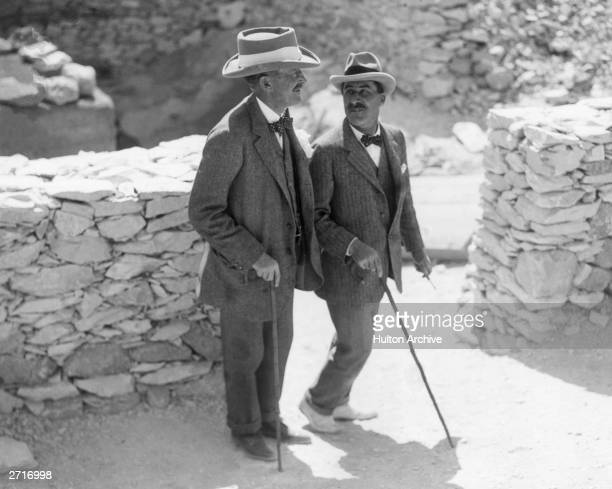 English Egyptologist Howard Carter walks with the patron of his research archaeologist and 5th Earl Lord Carnarvon George Herbert at the Valley of...