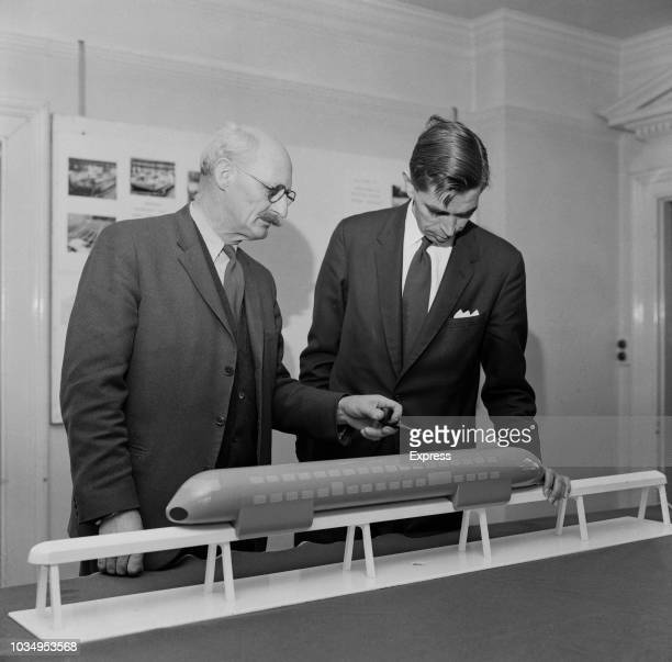 English engineer and inventor Christopher Cockerell pictured on left with Alan Pennington as they examine a model of a double decker hover rail car...