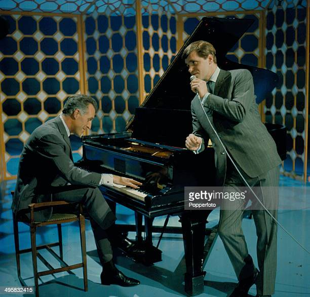English entertainer and presenter Bruce Forsyth performs at the piano with the singer Ronnie Carroll on the set of his television series 'The Bruce...