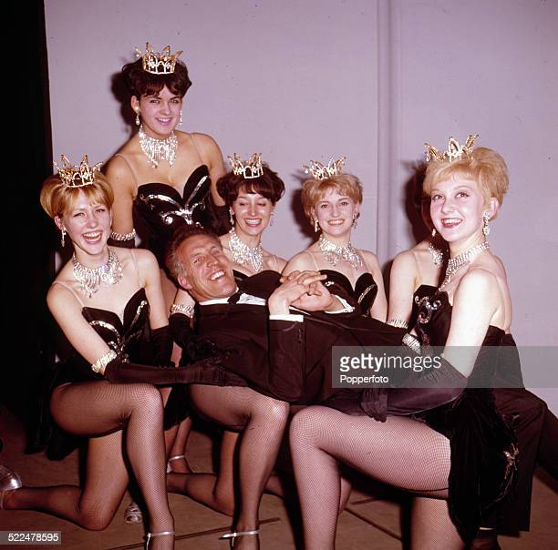 English entertainer and television presenter Bruce Forsyth pictured being supported by a troupe of chorus girls in London in 1964