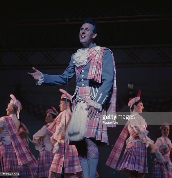 English entertainer and television presenter Bruce Forsyth pictured wearing a kilt and full highland dress on stage in London in 1964