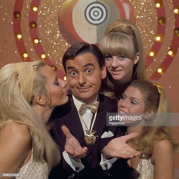 English entertainer Bob Monkhouse posed with three hostesses on the set of the televsion game show 'The Golden Shot' in 1967