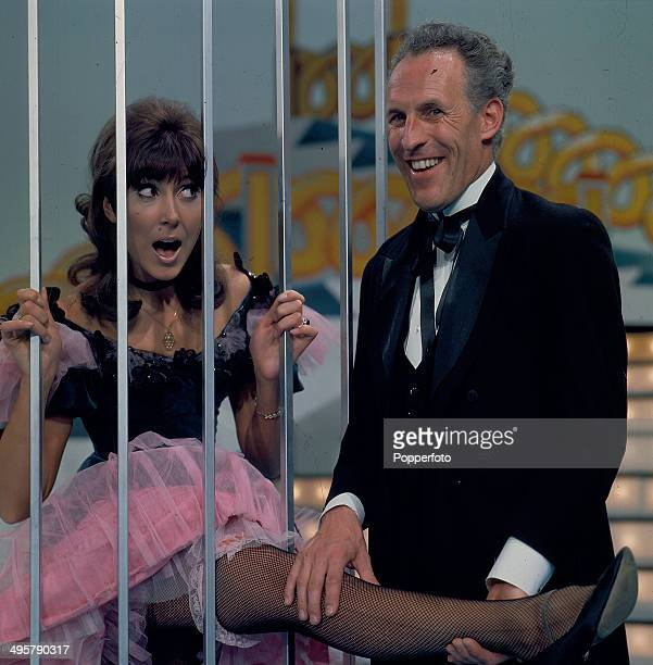 English entertainer Bruce Forsyth pictured with the actress and singer Anita Harris behind bars on the set of the television series 'The Bruce...