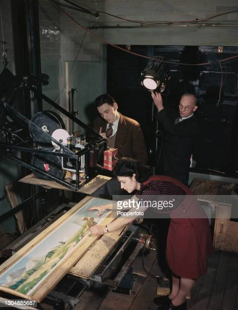 English entertainer, comedian and artist Bob Monkhouse , on left, watches rostrum camera operator Phyllis Isaacs place a cell on a background scene...