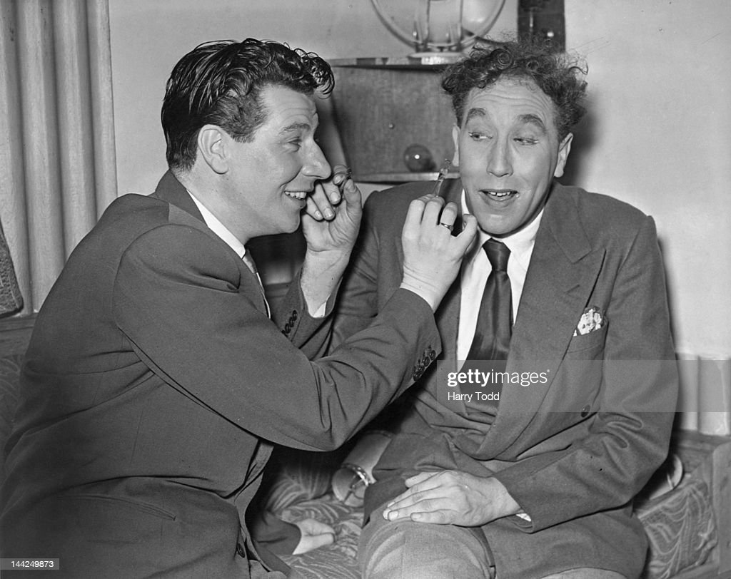 English entertainer Max Bygraves (left) and actor and comedian Frankie Howerd (1917 - 1992) helping each other with their make-up, backstage during rehearsals for the Royal Variety Performance at the London Palladium, 13th November 1950.