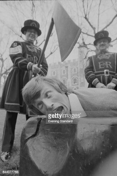 English entertainer Tommy Steele pretends to be decapitated by two Yeomen Warders at the Tower of London London UK 5th April 1978