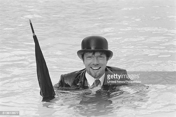 English entrepreneur and businessman Richard Branson pictured wearing a business suit and bowler hat whilst holding an umbrella in a swimming pool in...