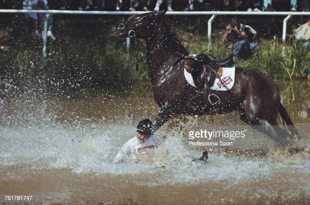 English equestrian Karen Straker pictured in action for the Great Britain team falling from her horse 'Get Smart' at the water jump during...