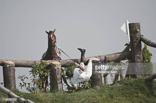 English equestrian Richard Walker competitor falls from his horse Jacanda as he attempts to negotiate a wooden hazard and grass slope during...