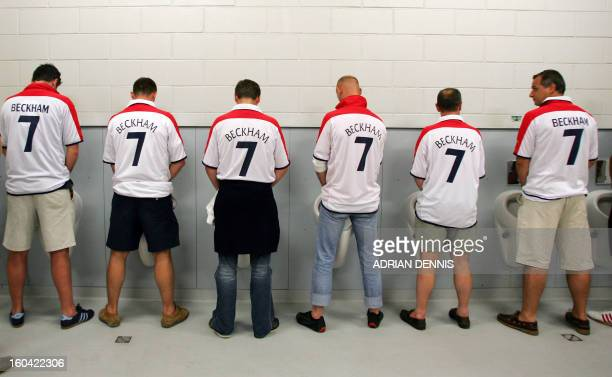 English fans from Belgium wearing David Beckham's number 7 jersey go to the toilet 21 June 2004 prior to the European Nations football championships...