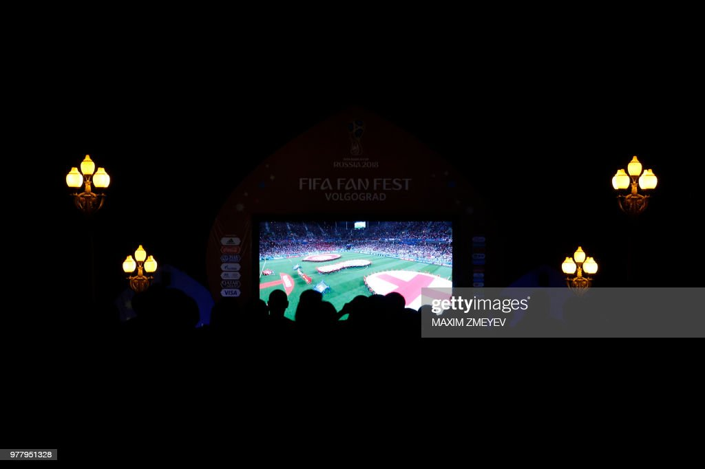 TOPSHOT - English fans in a Fan Fest watch the Russia 2018 World Cup Group G football match between Tunisia and England at the Volgograd Arena in Volgograd on June 18, 2018.