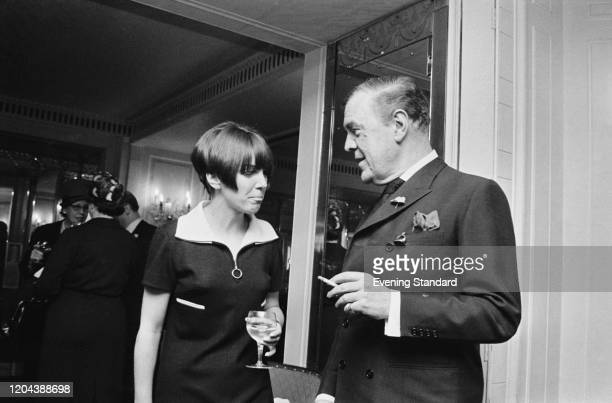 English fashion designer and fashion icon Mary Quant chatting with British fashion designer Norman Hartnell at a party, UK, 21st April 1966.