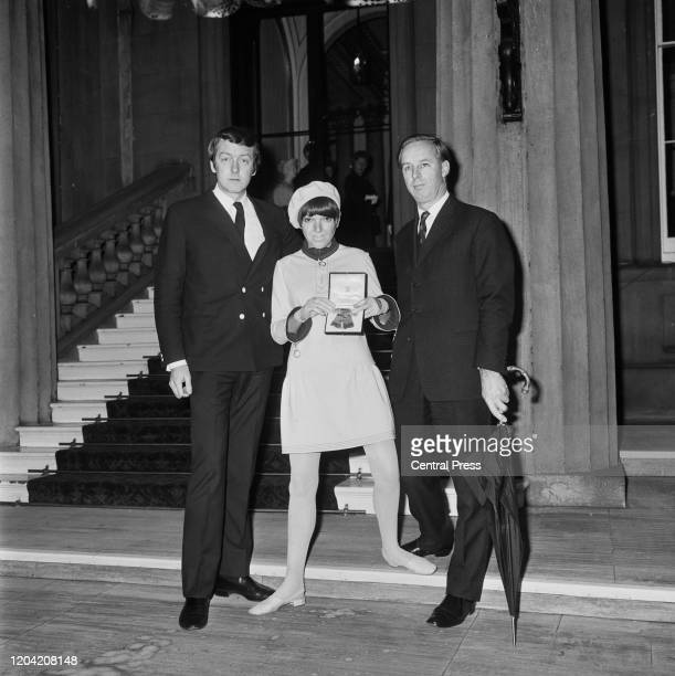 English fashion designer and fashion icon Mary Quant wearing wool jersey miniskirted dress and beret holds her OBE with her business partner and...