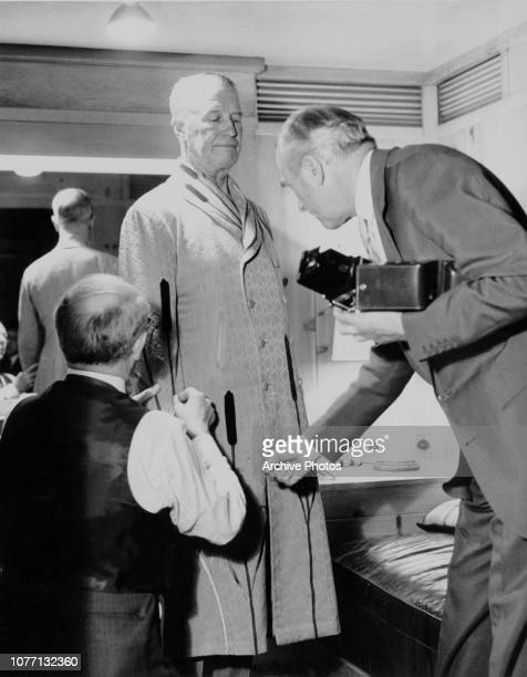 English fashion designer Cecil Beaton fits French actor and singer Maurice Chevalier with a coat on the set of the MGM film 'Gigi' circa 1958