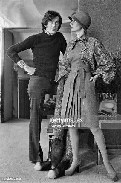 English fashion designer John Bates with a model in a pleated dress and cloche hat, UK, 2nd April 1973.