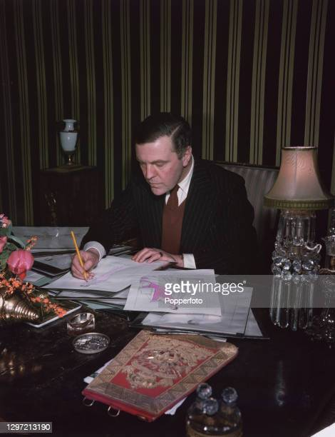 English fashion designer Norman Hartnell works on sketches of designs for the Queen's and Princesses wardrobe for the upcoming royal tour of South...