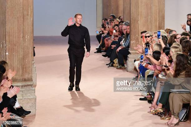 English fashion designer Paul Andrew acknowledges applause following the presentation of Salvatore Ferragamo's Women Fall - Winter 2020 fashion...
