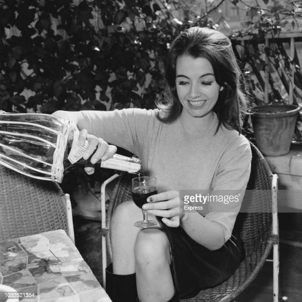 English fashion model and showgirl Christine Keeler pouring herself a glass of red wine, Madrid, Spain, 12th June 1963.
