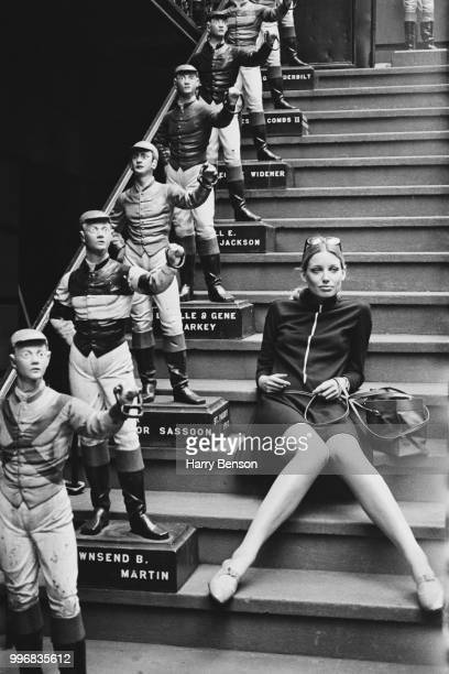 English fashion model Jane Lumb pictured seated on a staircase beside lawn jockey statues at the 21 Club in New York on 4th October 1967