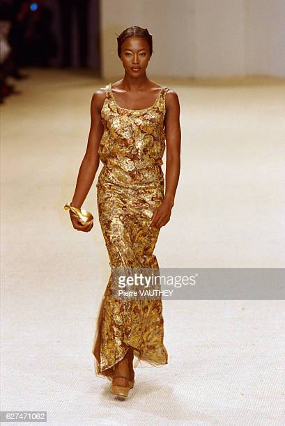 English fashion model Naomi Campbell wearing a women's haute couture gold dress designed by German fashion designer Karl Lagerfeld for French fashion...