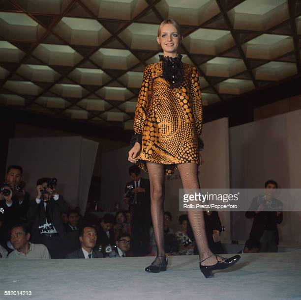 English fashion model Twiggy pictured wearing a black and orange mini dress with a lace ruff collar on a catwalk during a fashion show at the Osaka...