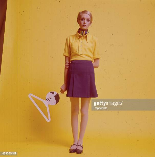 English fashion model Twiggy stands wearing a yellow shirt scarf and mini skirt and flat Mary Jane shoes whilst holding a coat hanger bearing her...