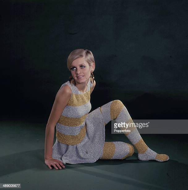 1967 English fashion model Twiggy wears a knitted silver and gold striped sweater skirt and matching lurex style stockings in 1967