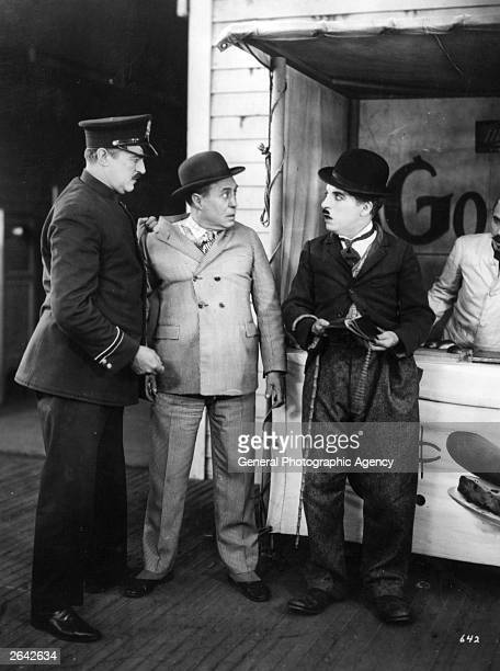 English film actor and director Charlie Chaplin gets involved with the police in a scene from the silent comedy 'The Circus' directed by himself for...