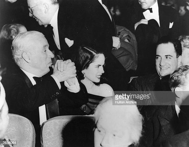 English film actor screenwriter and director Charlie Chaplin clasping his hands ecstatically whilst attending the premiere of his latest film...