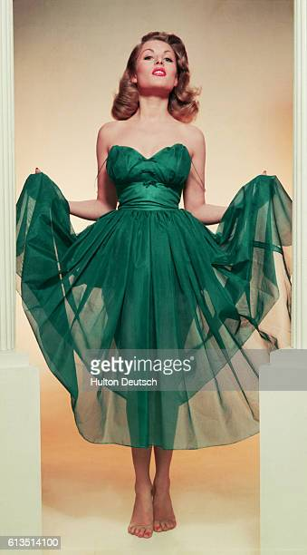 English film actress Belinda Lee modelling a blue chiffon evening gown