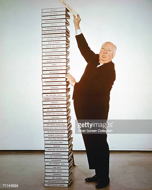 English film director Alfred Hitchcock adds the script of his latest film 'Torn Curtain' to a pile of scripts representing his career from 1925 to...
