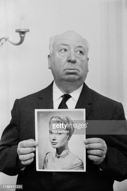 English film director Alfred Hitchcock holds up a photographic print of actress Grace Kelly in November 1964 Alfred Hitchcock is currently visiting...