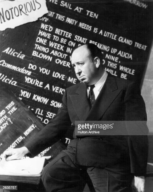 English film director Alfred Hitchcock in front of a board on which is written some of the script of his film 'Notorious'