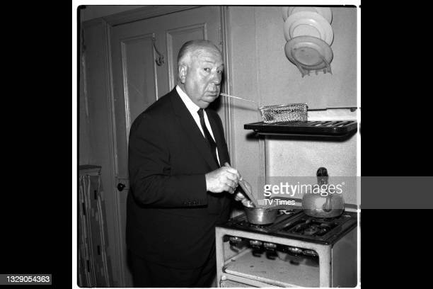 English film director Alfred Hitchcock photographed cooking at a stove on the set of television soap Coronation Street, at Granada Studios in...