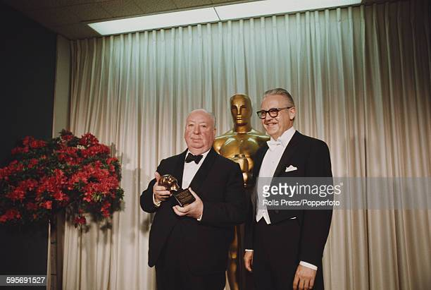 English film director Alfred Hitchcock pictured left standing with American film director Robert Wise at the 40th Academy Awards at the Santa Monica...