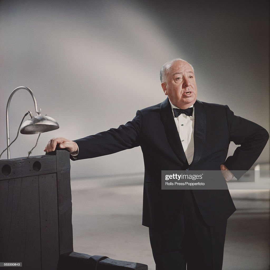English film director Alfred Hitchcock (1899-1980) pictured wearing a bow tie and smoking jacket and leaning against a mock electric chair type film prop in a film studio in 1965.
