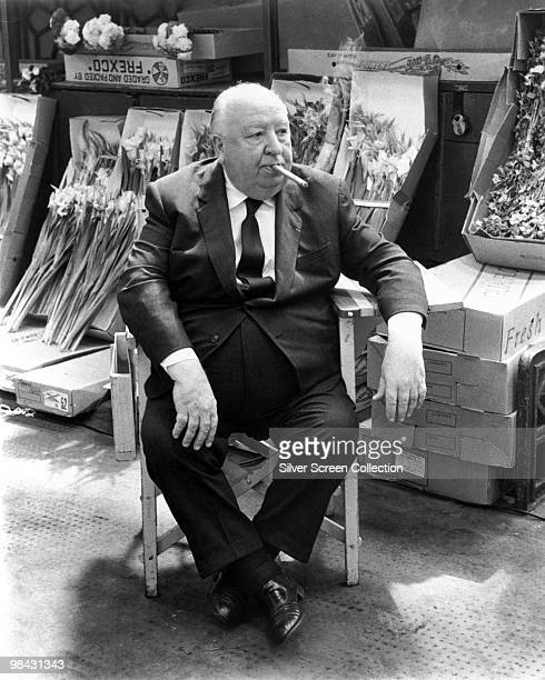 English film director Alfred Hitchcock surrounded by fresh flowers circa 1960