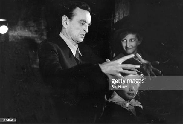 English film director David Lean demonstrating with his hands over the head of young actor John Howard Davies, how he wants a scene of his film...
