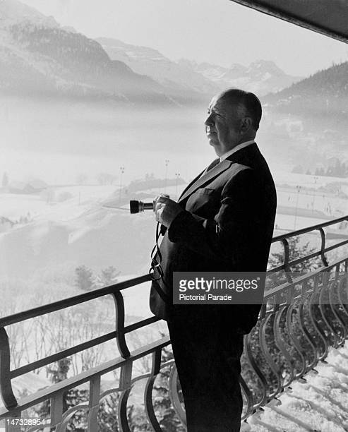 English film director director Alfred Hitchcock holding a camera as he admires the view from his balcony during a holiday in St Moritz Switzerland...